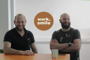 2 Kollegen sitzen zusammen am Tisch und haben Spaß - Arbeiten bei brickfox